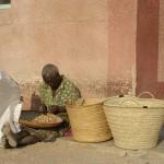 Le donne sbucciano le noccioline (Karanga) fuori dalla missione in cambio di offerte